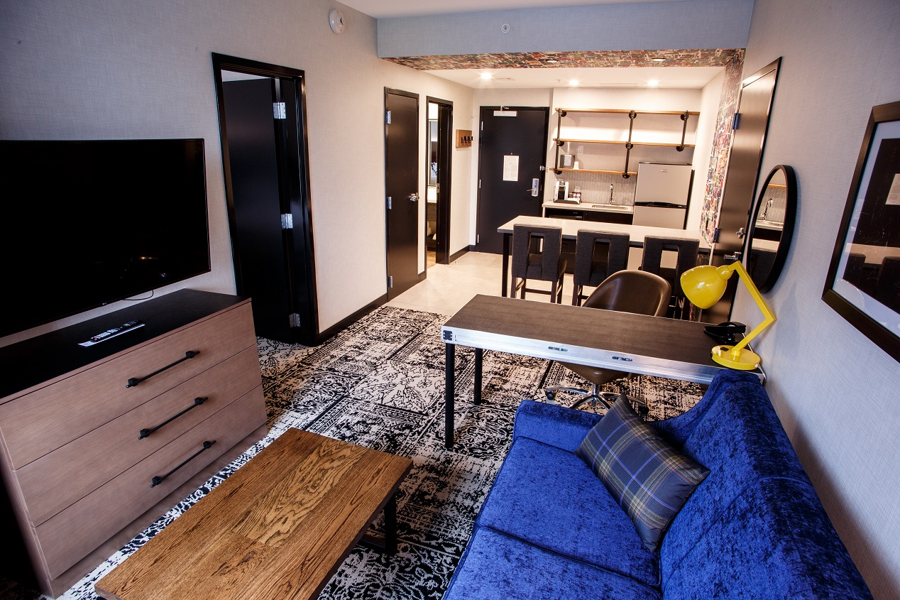 Hotel Rock Lititz Diamond Suite featuring a kitchen, blue couch, desk area to complete work and a flat-screen television