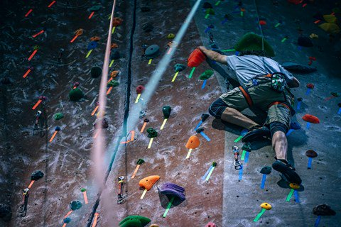 A young man climbing an indoor rock wall